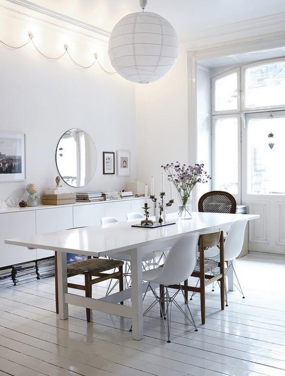Une salle à manger toute blanche à l'exception de deux ou trois chaises en bois ou osier