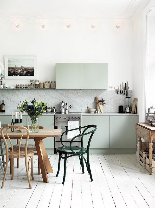 Cuisine pastel, table et chaises en bois à l'exception d'une chaise verte