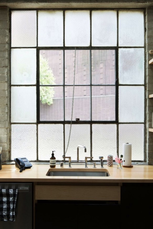 Une cuisine aménagée dans un loft murs en ciment brut et bois