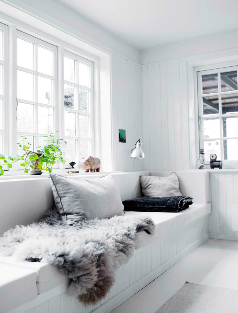 Une maison de campagne en blanc et noir sur fond de verdure // Banquette au bord de la fenêtre avec sa peau de mouton