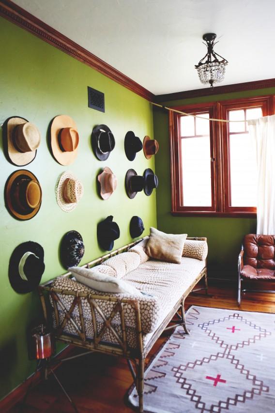 Collection de chapeaux sur mur vert