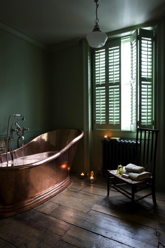 Salle de bain Shutters avec sa baignoire en cuivre et murs verts sapin