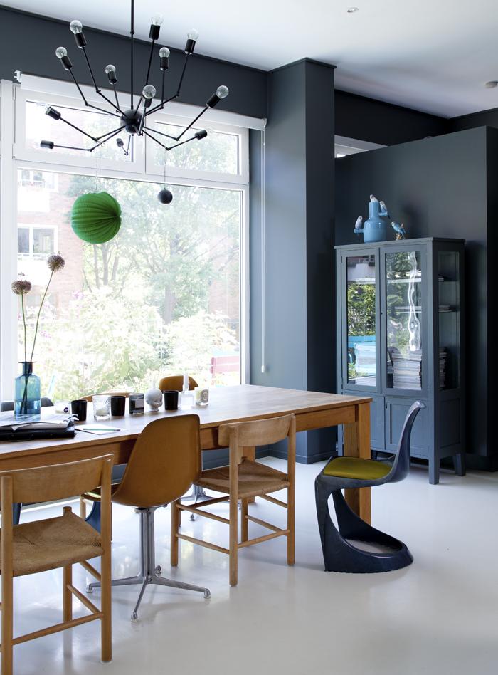 Un intérieur scandinave aux murs sombres avec un mixe and match de chaises ton bois et noir