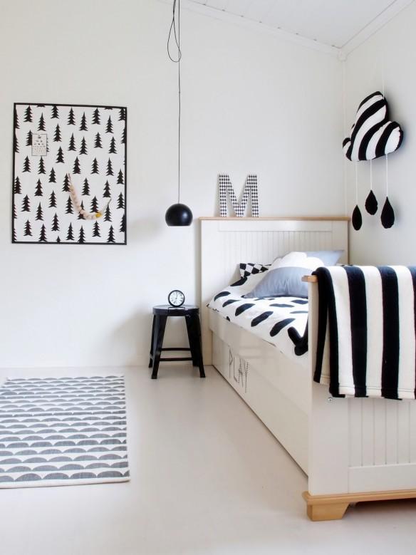 Chambre d'enfant blanche avec accessoires en noir et blanc