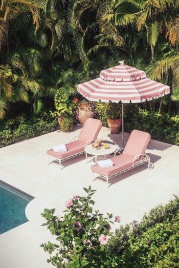 Transats et parasol roses au bord de la piscine