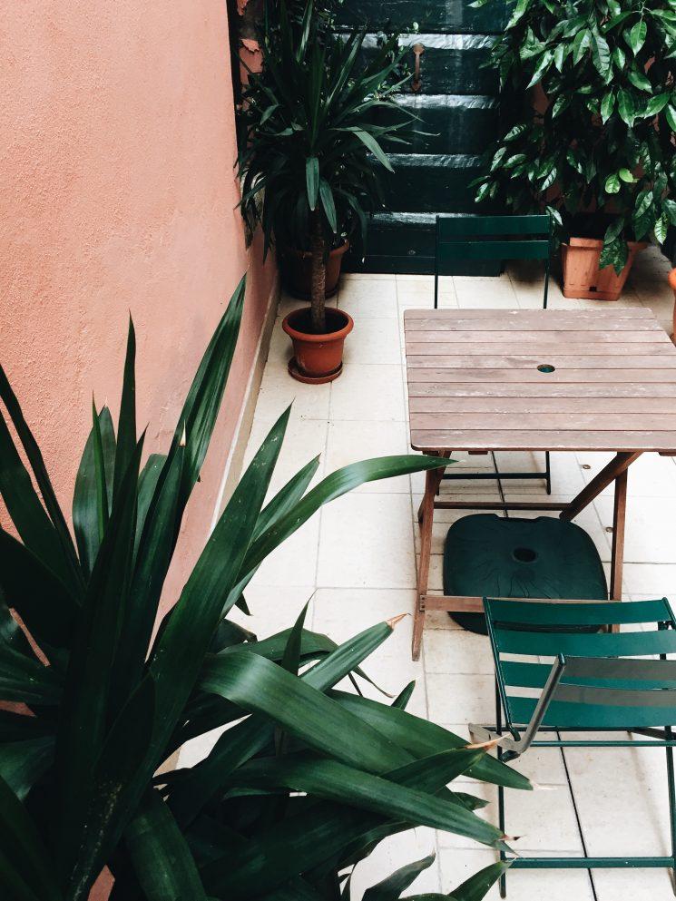 Patio au mur rose et mobilier de jardin vert