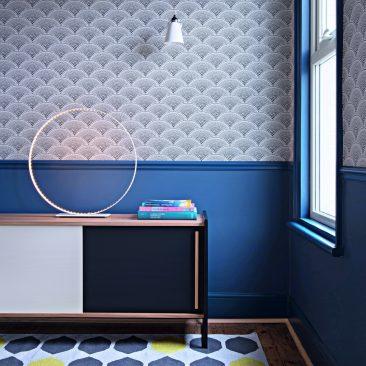Un intérieur aux sous-bassements et huisseries bleu roi et papier-peint noir et blanc Cole & Son