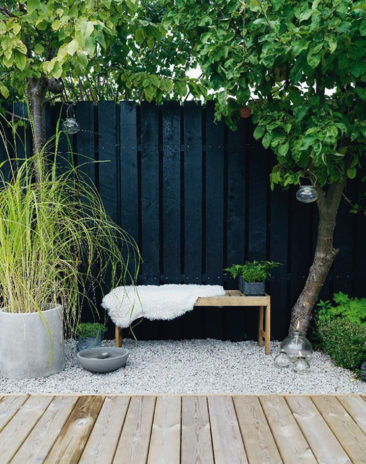Une palissade peinte en noir, quelques pots, un banc en bois et des graviers