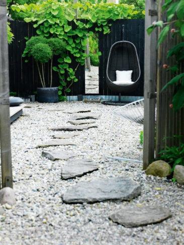 Une palissade peinte en noir, quelques pots et des graviers façon jardin japonais