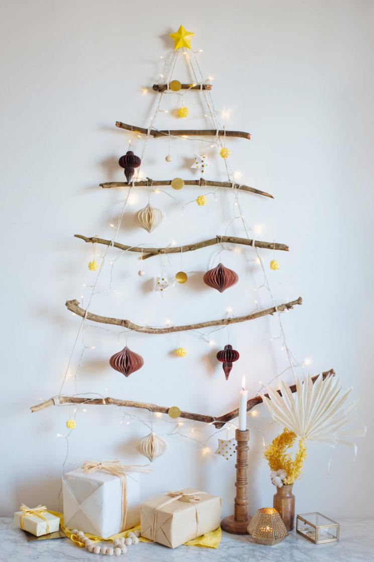 Un sapin de Noël à réaliser avec des branches , de la ficelle et un clou, à retrouver sur collectivegen.com