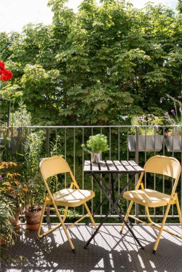 Aménager un balcon plein de charme - Une petite table bistrot avec des chaises de jardin dépareillées colorées