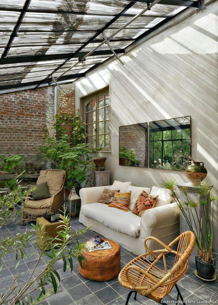 Aménager un jardin d'hiver dans sa véranda // Véranda dans une maison du nord, aménagée en salon cosy avec des meubles confortables et de nombreuses plantes