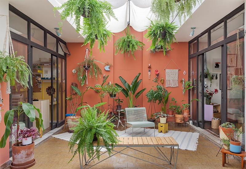 Aménager un jardin d'hiver dans sa véranda // Une cour intérieure avec verrière de toit, ravivée par un mur terracotta
