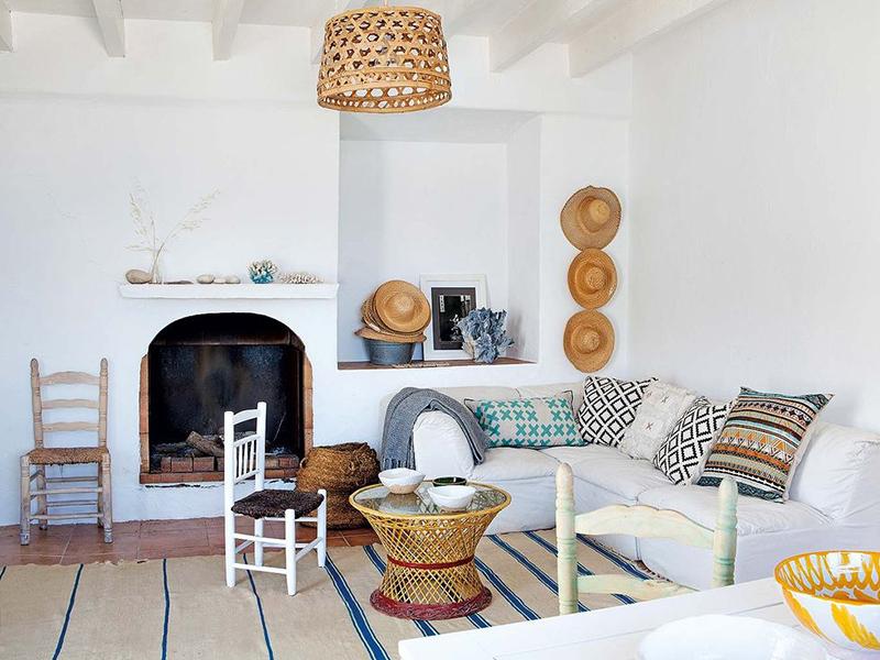 Une maison de pêcheur, rénovée par Jessica Bataille à Alicante // Tapis rayé en blanc et bleu et coussins ethniques, collection de chapeaux de paille