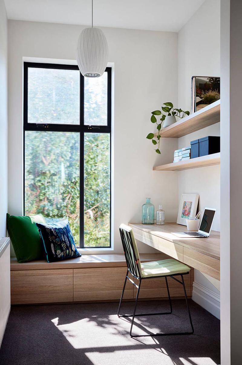 Un petit bureau aménagé dans une petite pièce avec son banc en dessous de la fenêtre