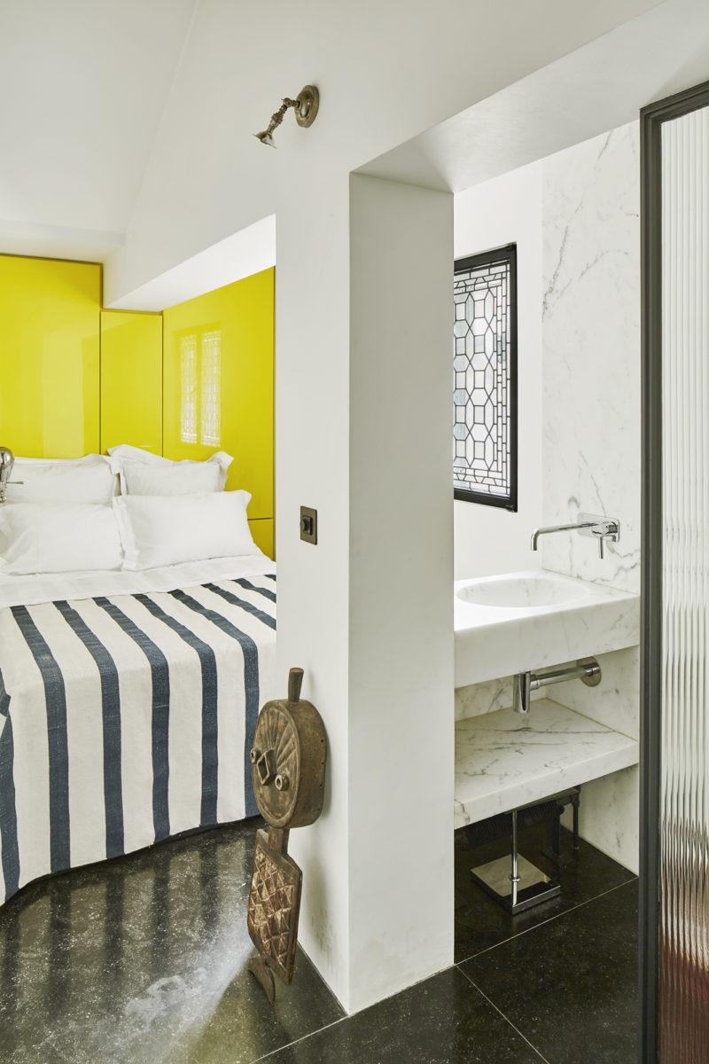 Chambre avec un fond de placards jaune vif pour cette petite chambre