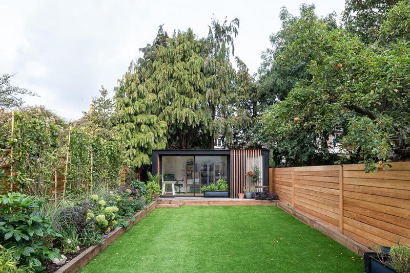 Une maison londonienne à l'intérieur familiale et design // On notera la cabane en préfabriqué au fond du jardin, qui sert de bureau
