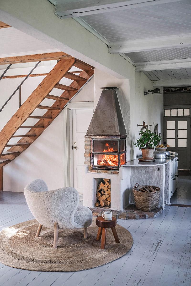 Le style scandi rustique et industriel en déco // La maison en suède du duo d'Our food stories - Petit coin cosy avec son poêle à bois et son fauteuil scandinave