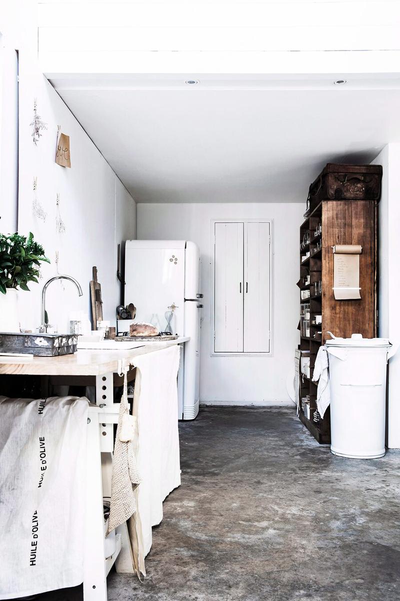 Une maison de mer,à Sydney à la décoration scandinave industrielle // Cuisine blanche au sol en béton ciré avec du mobilier de récup