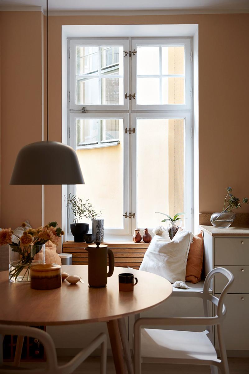 Palette de couleurs terracotta, rose, beige et brun // Coin repas dans une cuisine qui mixe les tonalités terracotta et nude avec du blanc pour apaiser