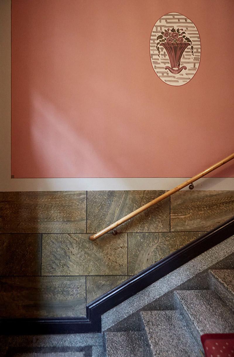 Palette de couleurs terracotta, rose, beige et brun // Escalier d'immeuble qui mixe un mur peint en rose et de la pierre vert gris