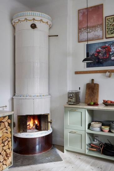 Un appartement ancien à Stockholm, plein de charme - Cuisine suédoise, avec placards verts d'eau et son poêle traditionnel en faïence