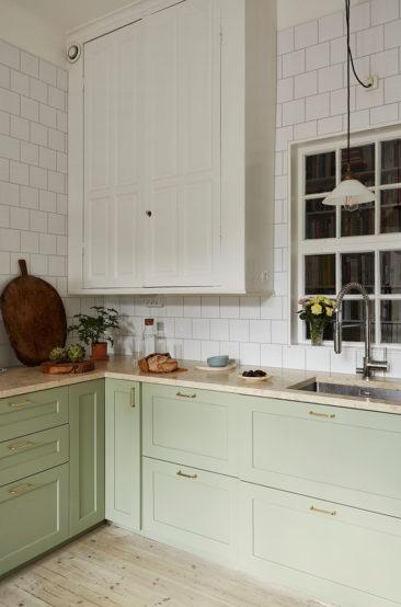 Un appartement ancien à Stockholm, plein de charme - Cuisine suédoise, avec placards verts d'eau et faïence blanche posée en quinconce jusqu'au plafond