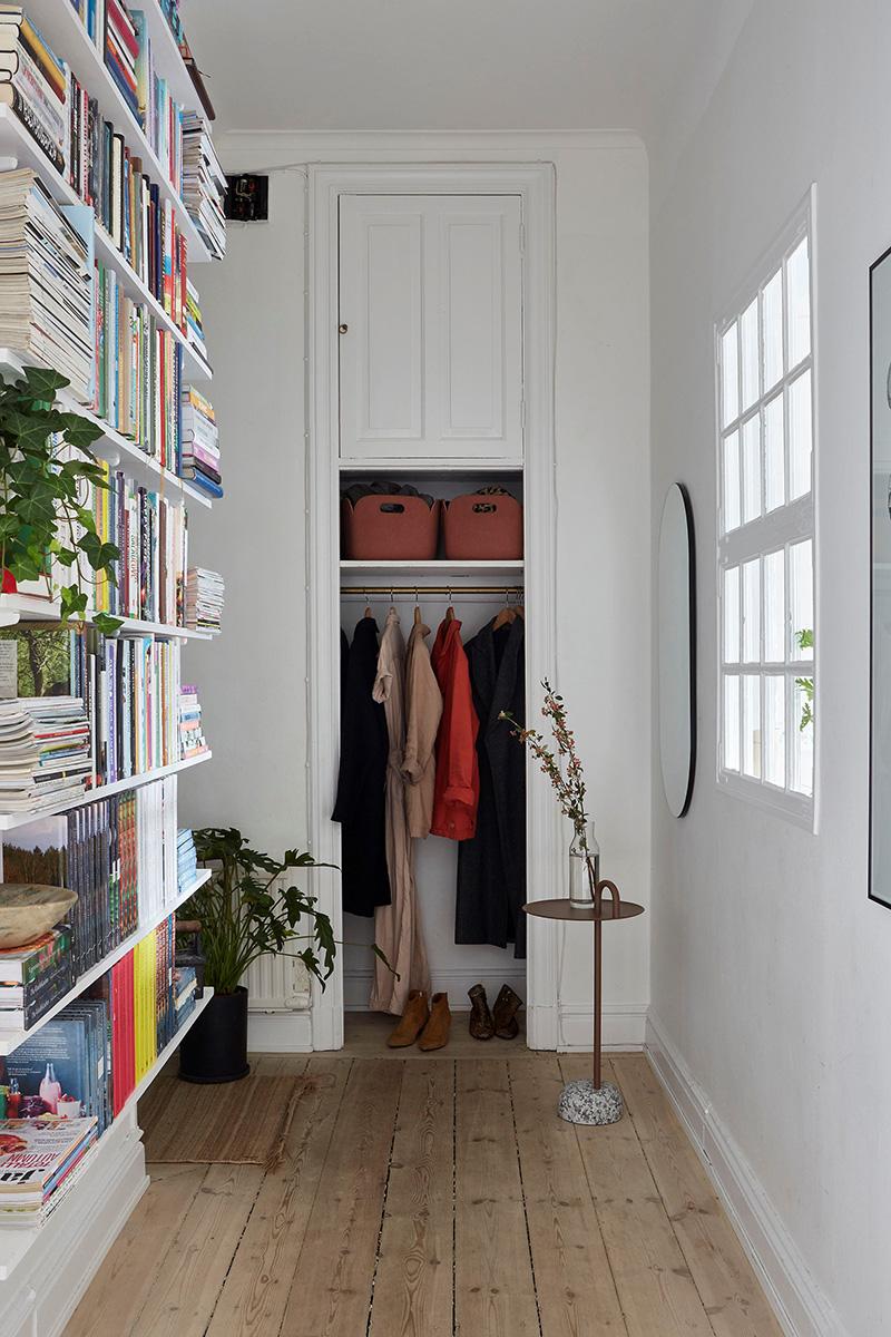 Un appartement ancien à Stockholm, plein de charme - Entrée avec bibliothèque basique et placard