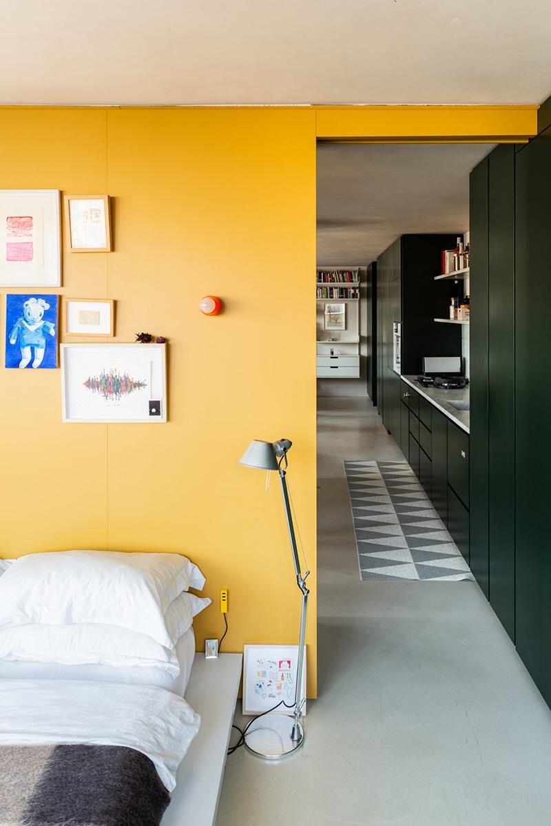 L'aménagement d'un appartement tout en longueur // Une chambre séparée par un meuble sur-mesure jaune et portes à galandages