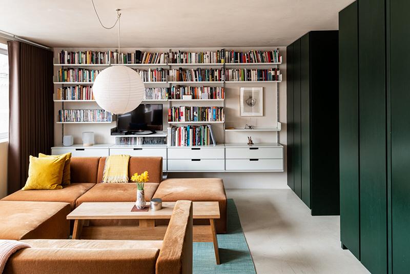 L'aménagement d'un appartement tout en longueur // Le salon présente un meuble télé bibliothèque