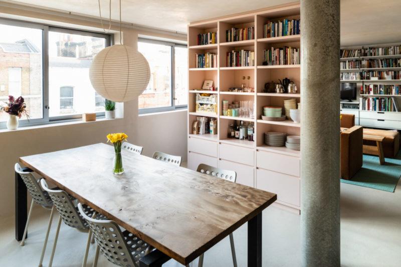 L'aménagement d'un appartement tout en longueur // Le salon et la salle à manger, séparées par un meuble sur-mesure rose