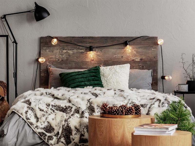 Une guirlande guinguette au dessus d'une tête de lit en bois recyclé, pour une ambiance douce