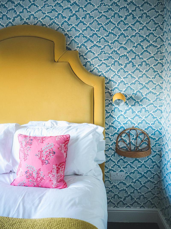 L'hôtel The Rose Deal par Nicola Harding // Tête de lit jaune sur papier-peint bleu et blanc Farrow&Ball