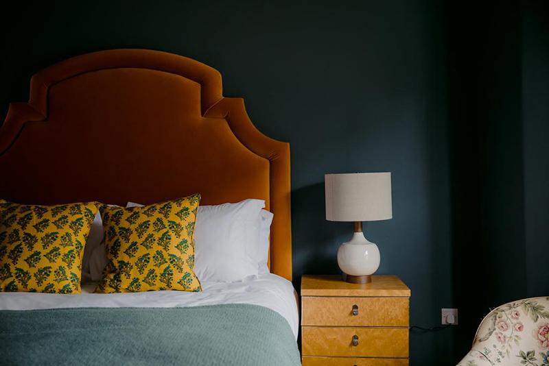 L'hôtel The Rose Deal par Nicola Harding // Tête de lit, tapissé de velours orange sur mur bleu paon