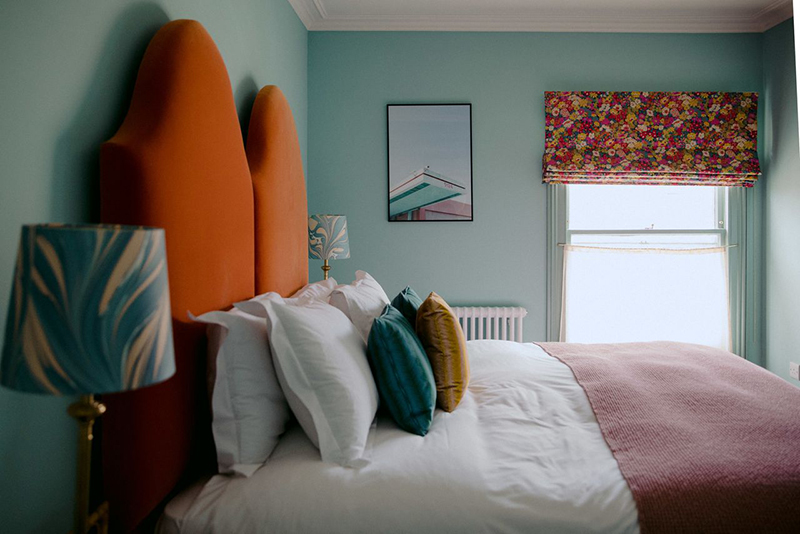 L'hôtel The Rose Deal par Nicola Harding // Tête de lit orange sur murs bleu aqua
