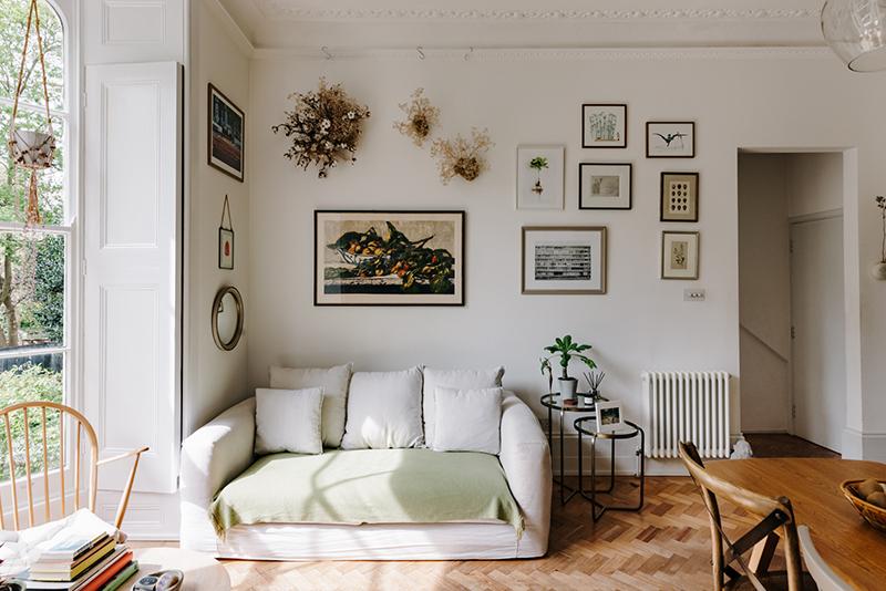 Coin salon à l'esprit scandinave avec son canapé blanc et sa mise en scène de cadres