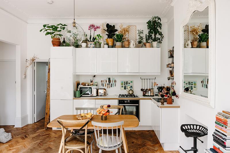 Cuisine laquée blanche, en L, avec une série de plantes placées au dessus des placards