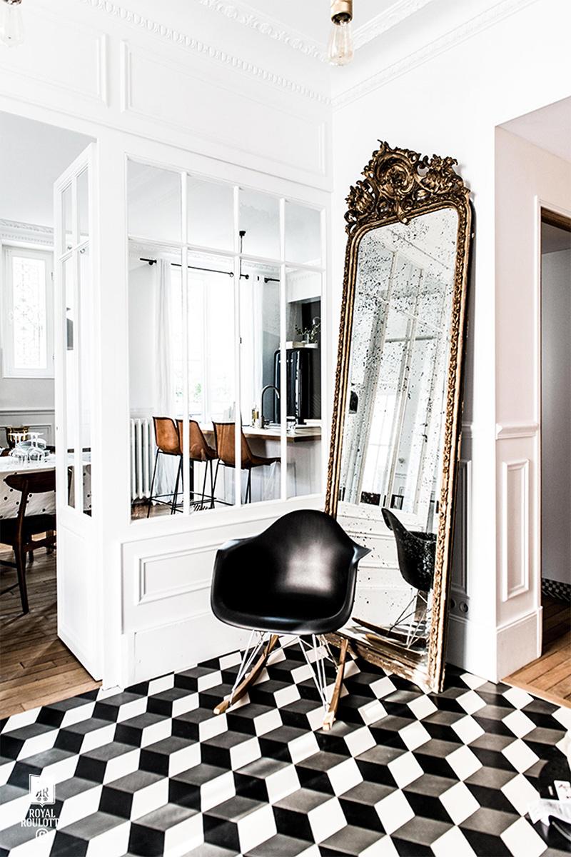 Un grand miroir trumeau posé à même le sol dans une entrée en carreaux de ciment noir et blanc par Royal roulotte