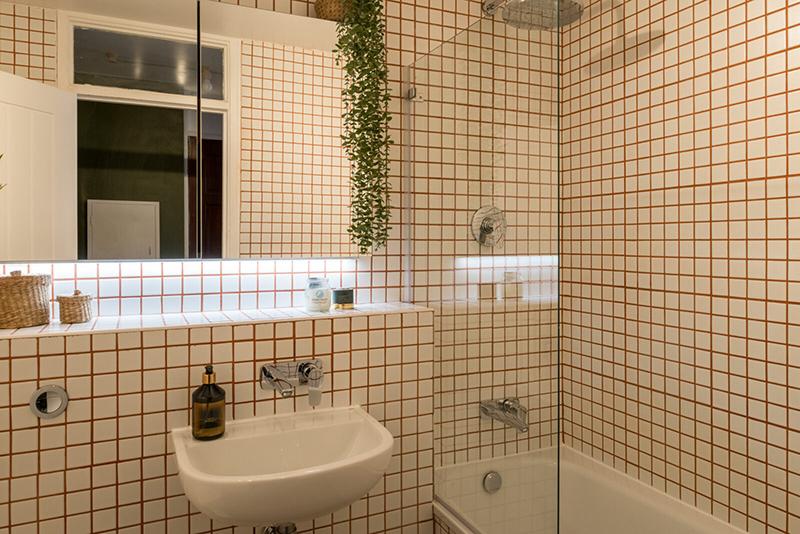 Salle de bains à petits carreaux de faïence blancs et joints rouge à l'aeffet graphique