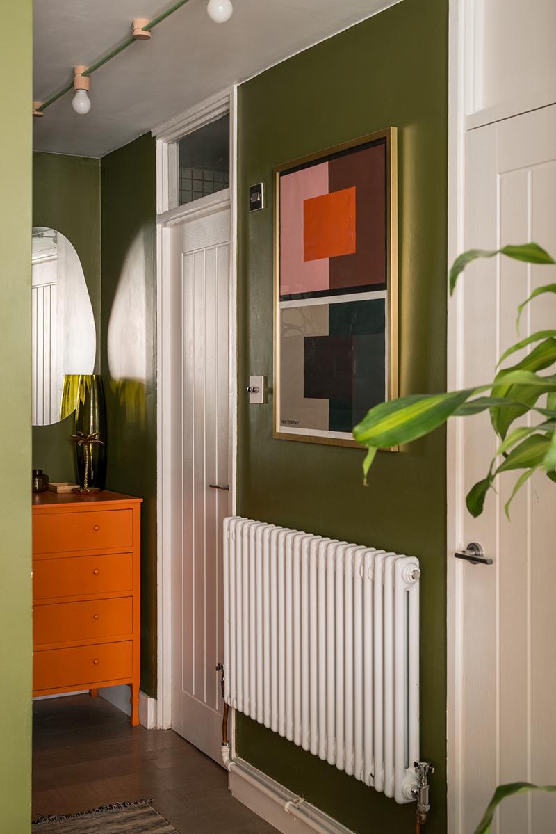 Entrée en vert et blanc, boosté par un meuble orange et un tableau graphique coloré