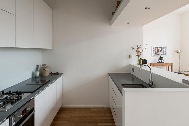 Placement de spots encastrés sur l'imposte d'une cuisine, afin d'éclairer un plan de travail