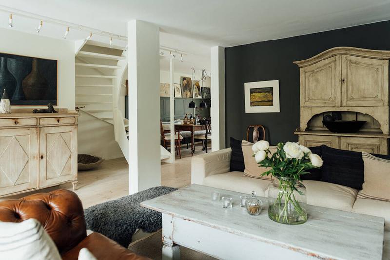 Une maison parfaitement lagom en Suède // Un salon en noir et blanc adouci par des meubles en bois décapé